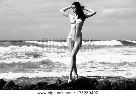 Pretty Girl In Sexi Swimsuit Standing On Rocky Beach