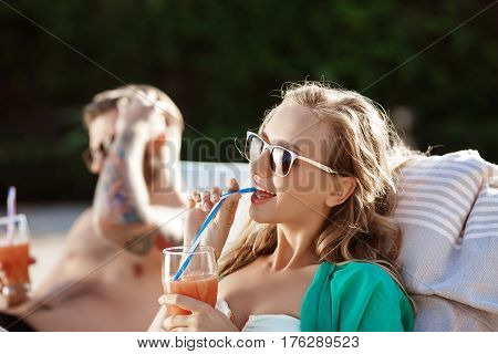Young friends smiling, sunbathing, drinking cocktails, lying on chaises near swimming pool. Copy space.