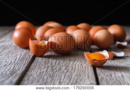 Fresh chicken eggs on wood at black background. Brown and white eggs with cracked eggshell and yellow yolk on rustic table, copy space. Rural still life, natural healthy food concept.