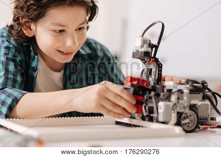 My digital friend . Skilled cheerful charming boy sitting in the studio while expressing joy and constructing robot