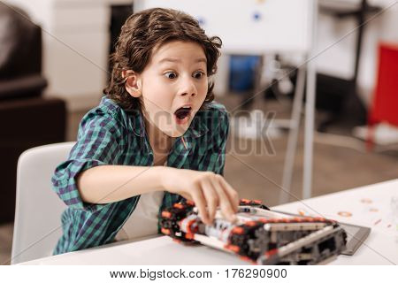Expressing real amazement. Amazed cute funny boy sitting in the studio and touching device while programming robot