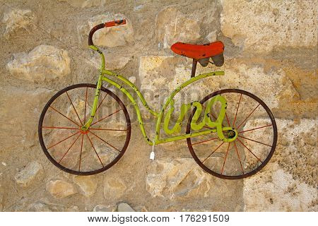 Besalu Spain - September 09 2014: A decorative green bicycle model hanging on stone wall for sale in the market of Besalu (Catalonia Spain)