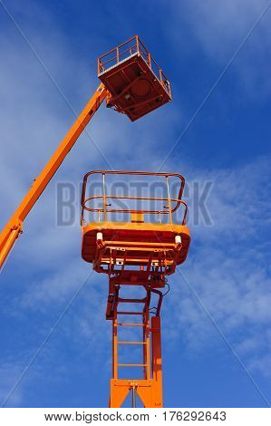 Lift platform with bucket and cherry picker aerial work platforms, construction hydraulic telescopic cranes of orange and white colors, heavy industry, white clouds and blue sky on background