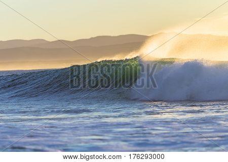 Ocean wave crashing along beach coastline morning back lit colors