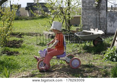 Cute girl playing outdoors with a bike and an old bucket helmet