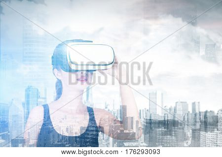 Double exposure of woman using a VR-headset while standing against a morning city panorama. Double exposure mock up