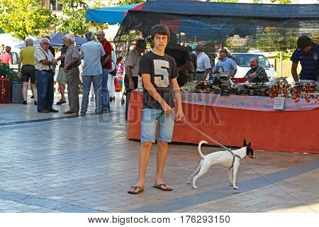 Besalu Spain - September 09 2014: Young man with his pet in the market in Besalu (Catalonia Spain)