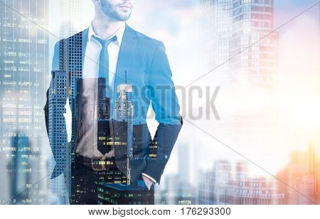 Double exposure of an unrecognizable bearded businessman with his arms in the suit pockets standing against a city panorama. Toned image. Mock up. Double exposure.