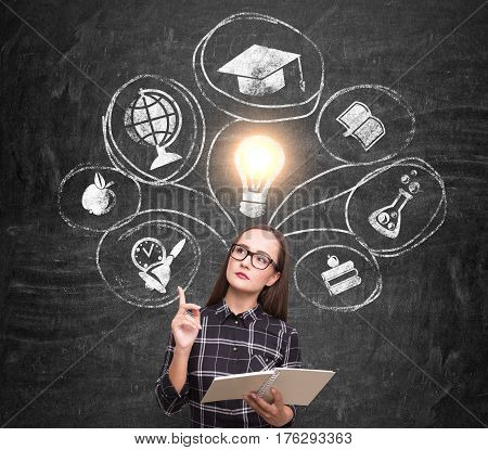 Portrait of a nerdy girl holding a book and wearing glasses while standing near a blackboard with education choice icons.