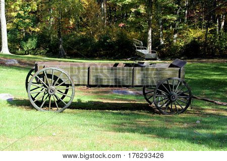 Large wooden 19th century farm wagon sitting on a green lawn on a sunny day.