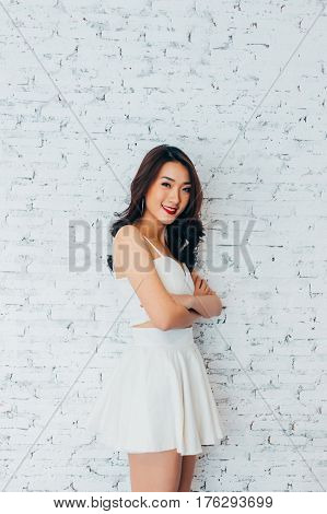 Young Happy Asian Woman Having Arms Folded And Smiling In Fashionable Dress