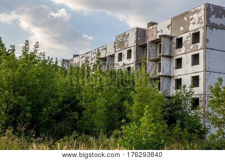 Abandoned and overgrown five-story house in ghost-town, summer, Russia, Samara region