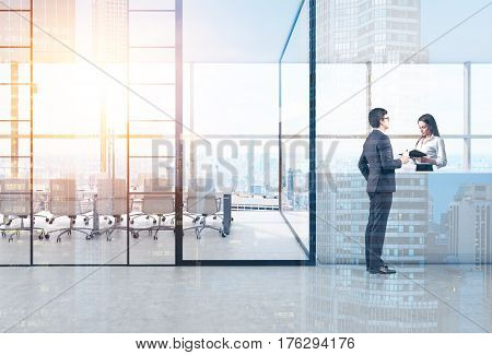 Side view of a businessman standing near a reception desk and talking to the receptionist. Toned image. Double exposure