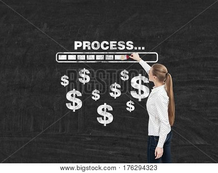 Rear view of a blond businesswoman drawing a progress bar and dollar signs on a blackboard. Concept of making money.
