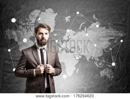 Portrait of a bearded businessman standing near ablackboard wtih a world map on it.
