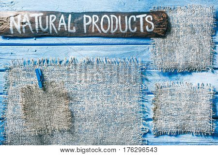 Burlap frames on blue painted wood boards. Dark wooden signboard with text 'Natural products' as title bar. Structured shabby style background for natural food and drink industry