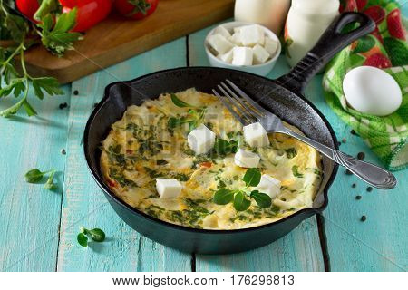 Omelette With Peppers, Tomatoes And Feta Cheese In A Cast Iron Frying Pan On A Wooden Table. The Con