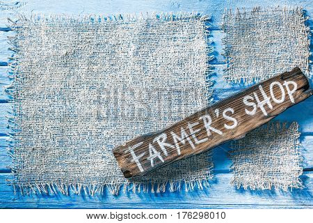 Burlap frames on blue painted wood boards. Dark wooden signboard with text 'Farmers shop' as title bar. Structured shabby style background for natural food and drink industry