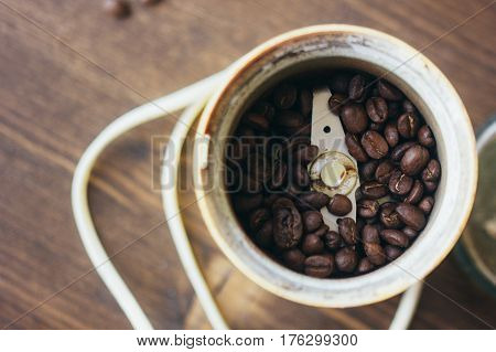 Electric Coffee Mill Machine With Coffee Beans Inside. Coffee Grinder Over The Kitchen Table.