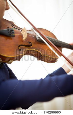 Young Girl plays violin on concert of classic music.