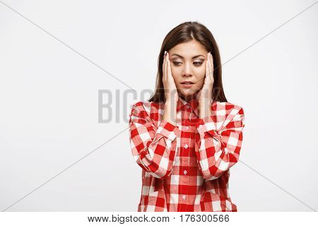 Young beautiful woman with strong tension headache holding headache looking down wearing red shirt