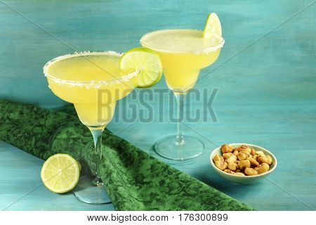 Lemon Margarita cocktails with wedges of lime and a salted nuts snack, on a vibrant turquoise background with copy space. Selective focus