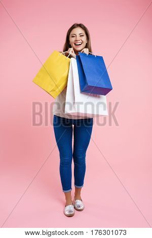 Laughing woman in basic look with denim trousers and white shirt looking straight with smile