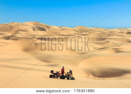 Two happy quad bikers driving in sand dunes. Young active couple in outdoor activity driving quad ATV in desert, Africa.