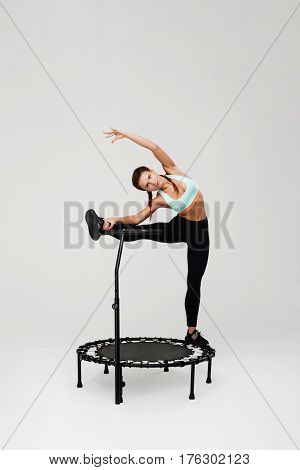 Sporty woman stretching muscles staying on rebounder with left leg on handle bending to left
