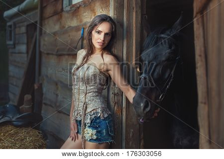 Woman and horse in a wooden shed in rural areas.