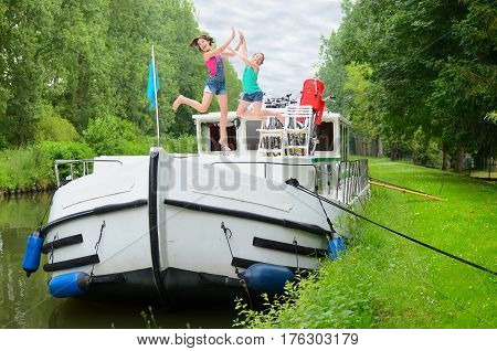 Family vacation, travel on barge boat in canal, happy parents with kids having fun on river cruise trip in houseboat