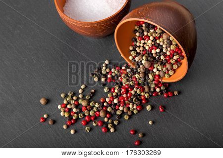salt and pepper in a clay bowl on a slate board pepper is scattered