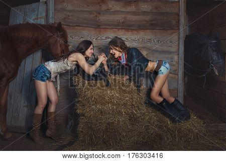 Two women wrestle on hands on a farm near the stables.