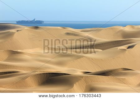 Sand dune desert meets water of the Atlantic Ozean. Container ship on the water.
