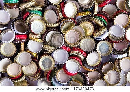 a lot of caps of beer randomly scattered background top view
