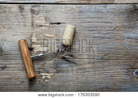 cork and corkscrew on a grunge wooden background. top view