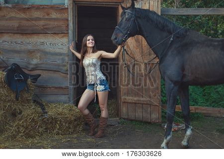 Cowboy woman is holding a horse by the bridle on the farm.