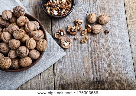 on a wooden table is a plate with walnut in thair shell beside it are cracked nuts and shells. the plate is stnding on the linen napkin.