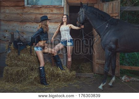 Stylish women cowboys in rural areas on farm with horses.