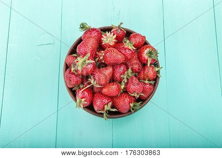 strawberry in a clay plate on wooden turquoise surface top view