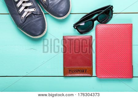 set for traveling passport e-book sneakers sunglasses. on a wooden turquoise surface a top view
