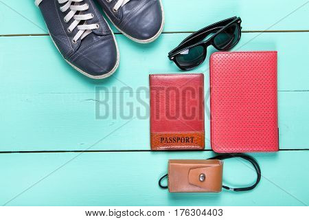 set for traveling passport e-book sneakers sunglasses camera. on a wooden turquoise surface a top view