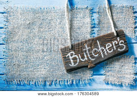 Burlap frames on blue painted wood boards. Dark wooden signboard with text 'Butchers' as title bar. Structured shabby style background for natural food and drink industry