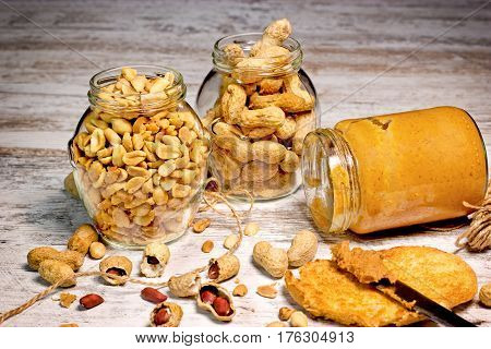Organic peanut, peanuts in shell in jar and peanut butter on rustic table