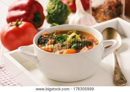 Vegetable soup goulash with meat on wooden table.