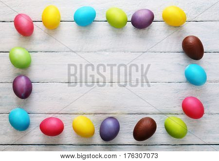 Multicolored eggs border copy space on white wooden background. Easter conceptual background. Top view