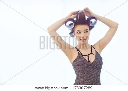 Girl in hair curlers in sexy dress and day make-up on white background. Portrait of a sexy woman preparing to party indoors at home against bright window
