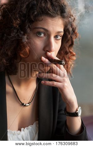 A beautiful young woman with blue eyes holding a Tuscan cigar looking into the camera