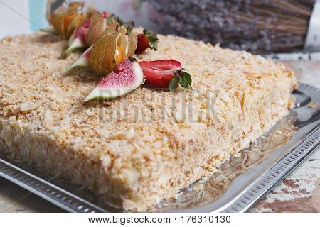 Homemade napoleon cake decorated with berries and flowers close up. Selective focus. Restaurant dessert menu background.