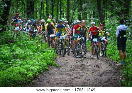 Lviv Ukraine - August 17 2016: O. Todorchak N2 D. Sokolov N4 E. Zakora N5 with Group of MTB cyclists on start line competing in the forest near Lviv in Ukraine at 4th round of amateur xc cup of Ukraine 2016.